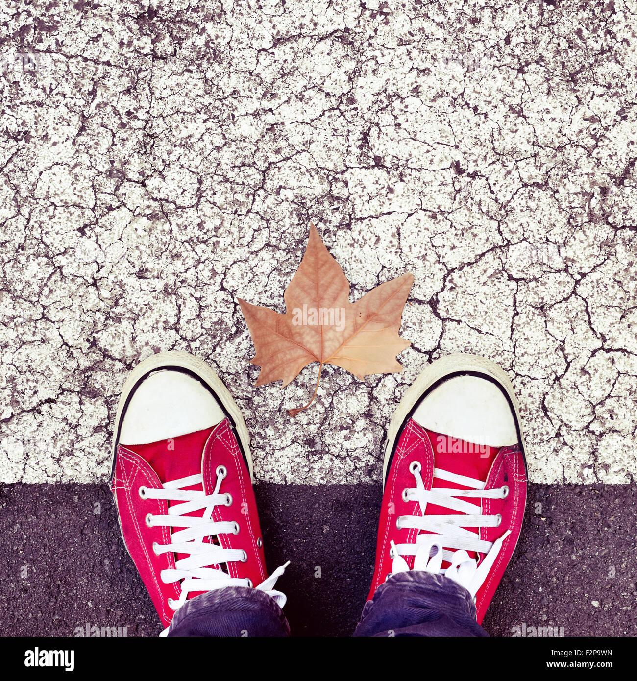 Alta angolazione di una foglia secca e i piedi di un uomo che indossa red sneakers sull'asfalto Foto Stock