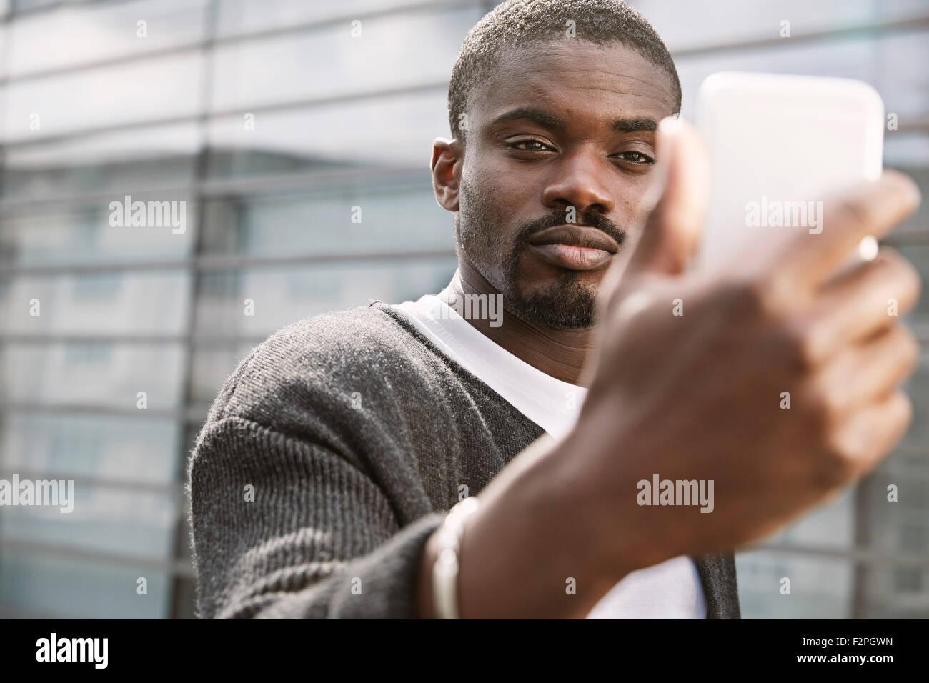 Giovane uomo prendendo un selfie all'aperto Immagini Stock