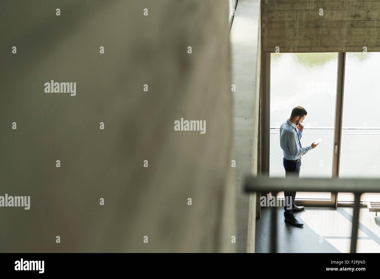 Giovane imprenditore cerca su telefono cellulare in corrispondenza della finestra Immagini Stock