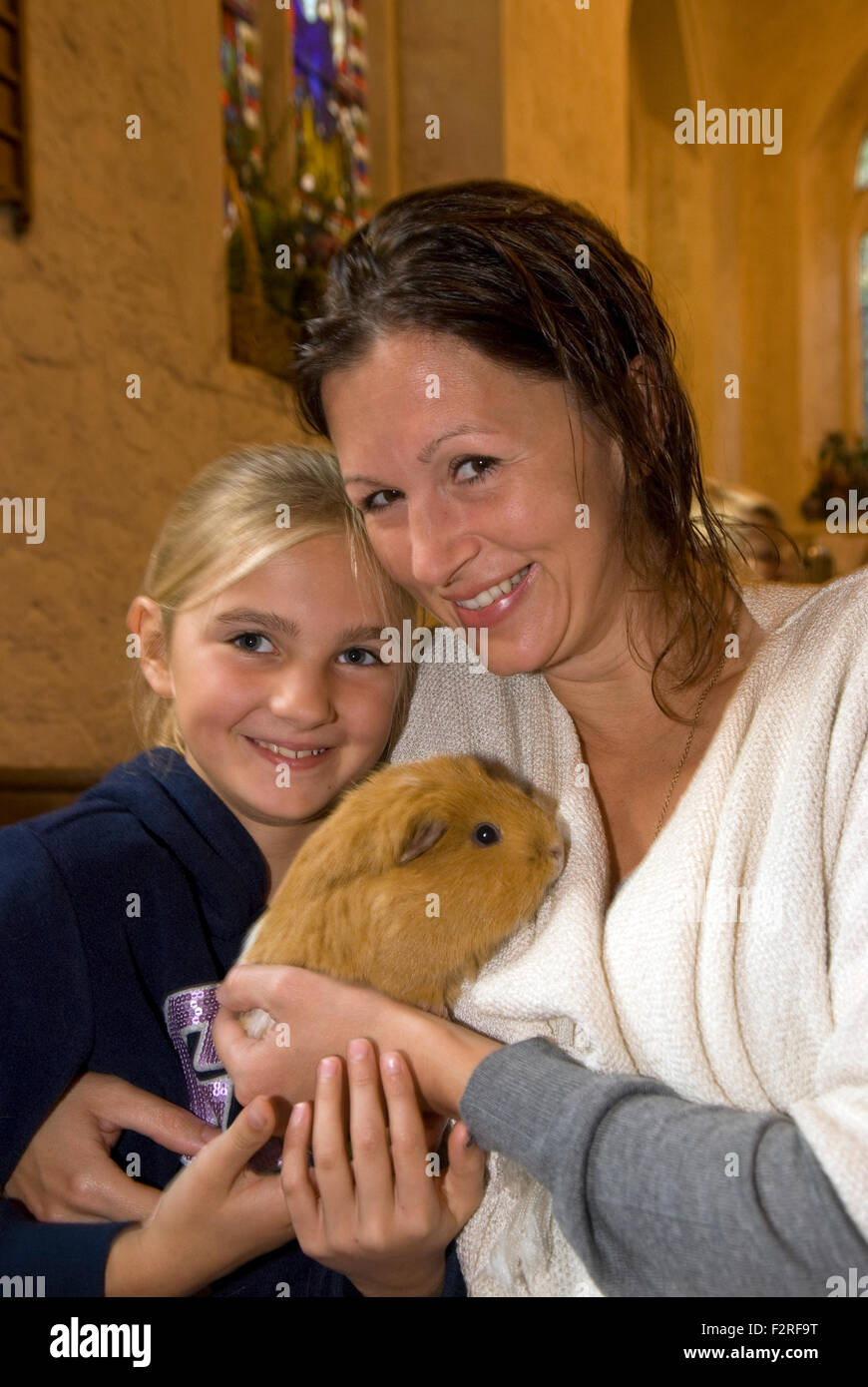 Madre e figlia di 10 anni e la loro cavia in un servizio di chiesa dove la congregazione sono stati invitati a portare Immagini Stock