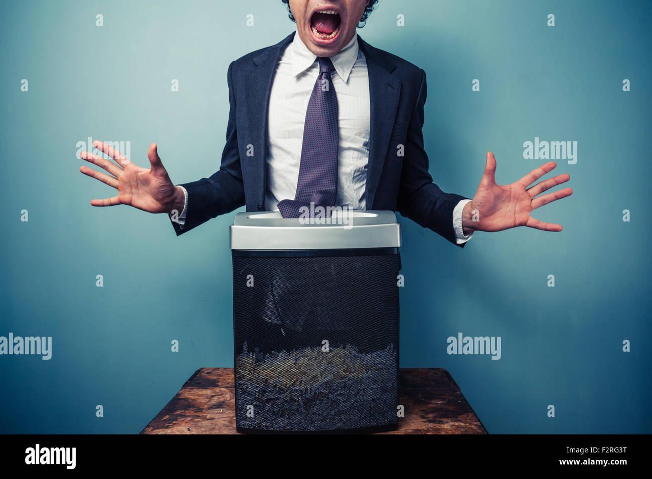 Imprenditore ha ottenuto il suo tirante bloccato in un foglio di carta trinciatrice Immagini Stock