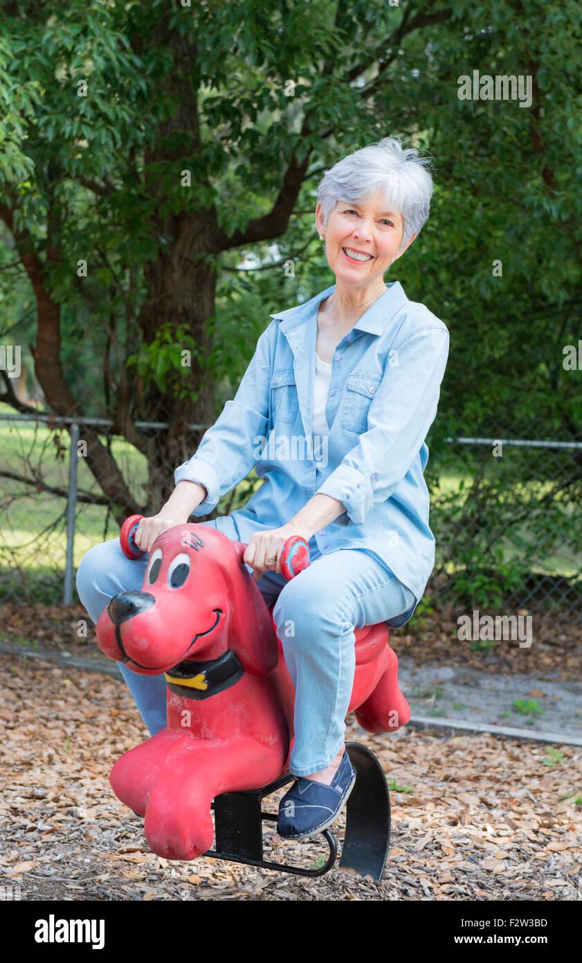 Ritirato donna nella sua 70's al parco giochi scherzosamente riding cane giocattolo Clifford Big Red Dog Modello Immagini Stock