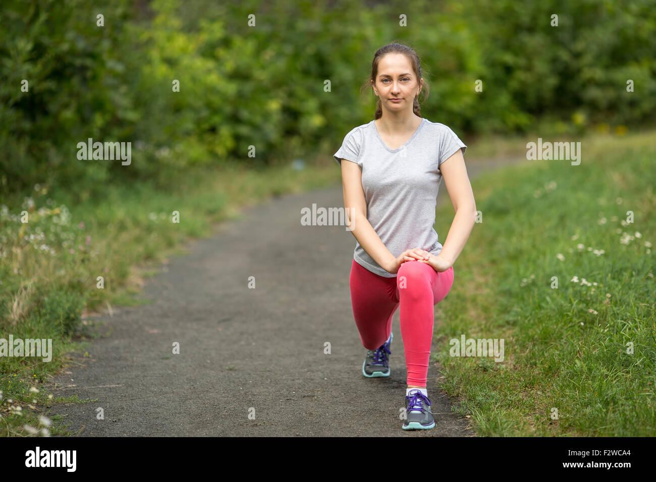 Giovane ragazza sportiva è in fase di riscaldamento all'esterno. Uno stile di vita sano. Immagini Stock