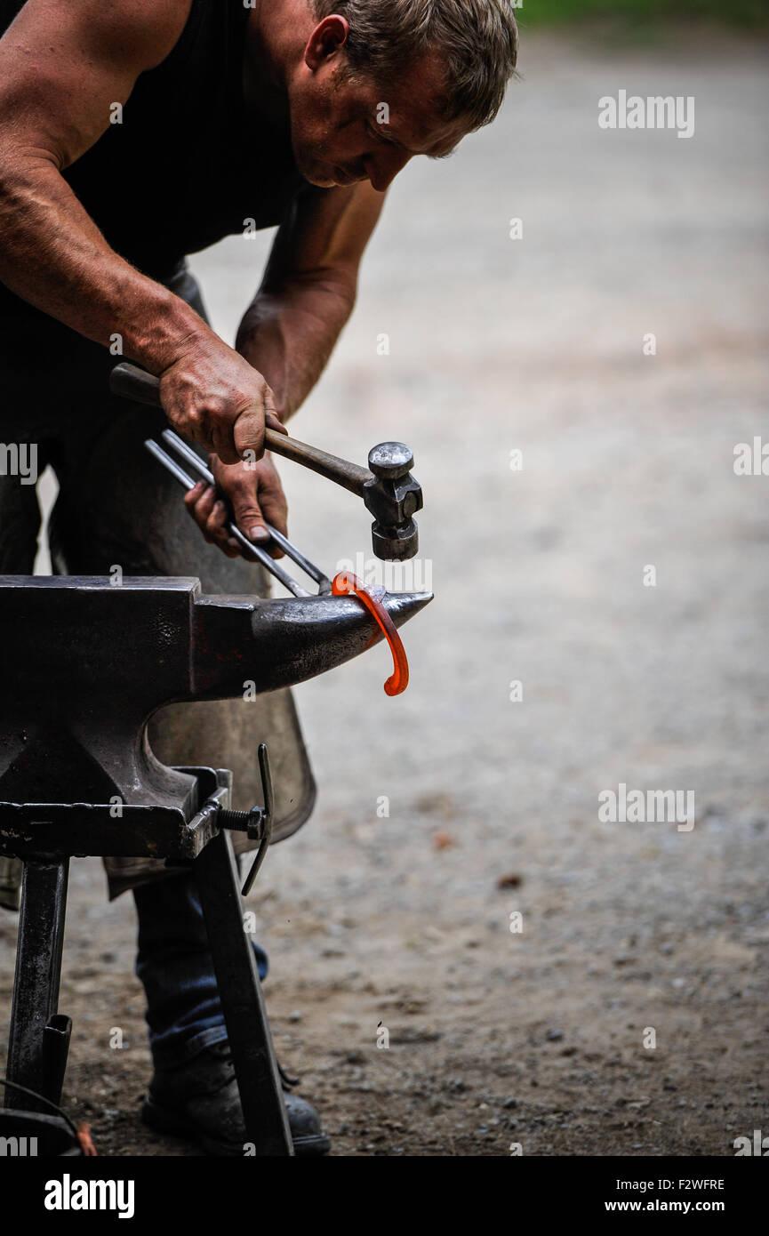 Un maniscalco in un duro lavoro re ferratura di cavalli, battito in testa di un ferro di cavallo fuso in posizione Immagini Stock