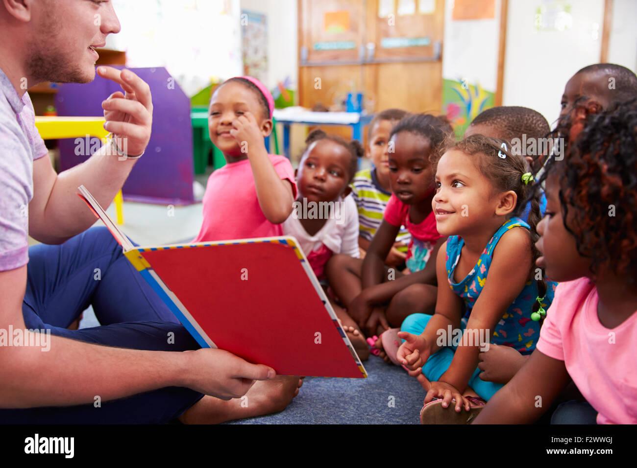 Maestro di volontariato lettura a una classe di bambini in età prescolare Immagini Stock