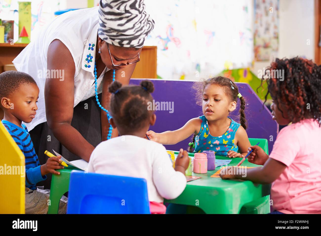 Insegnante aiuta i ragazzi in una classe di età prescolare Immagini Stock