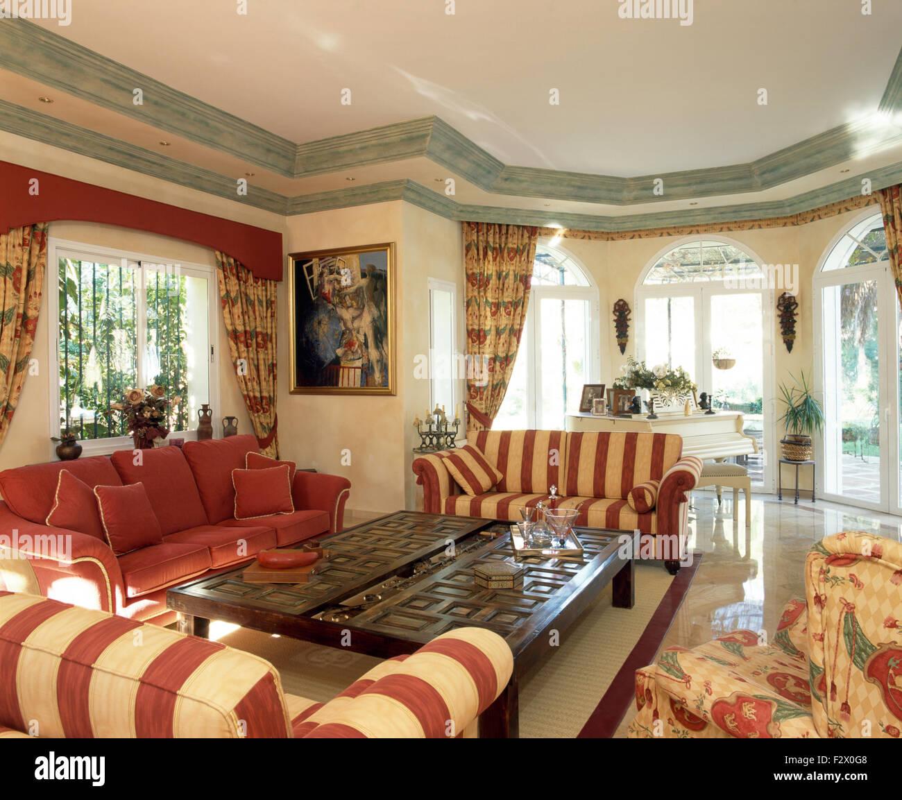 Rosso striato set divani intorno al legno intagliato tavolino in ...