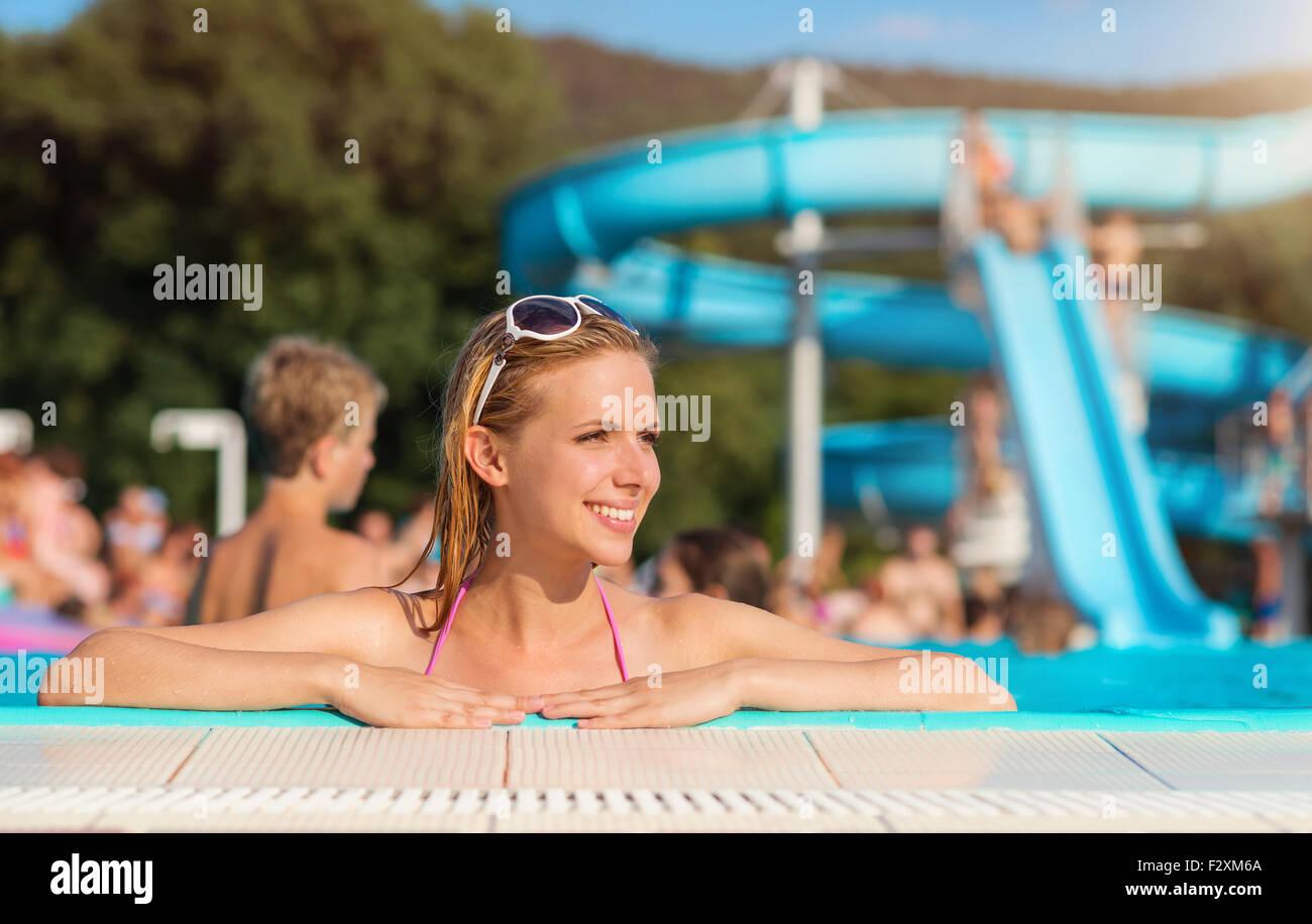 Bella giovane donna avente divertimento fuori in piscina Immagini Stock