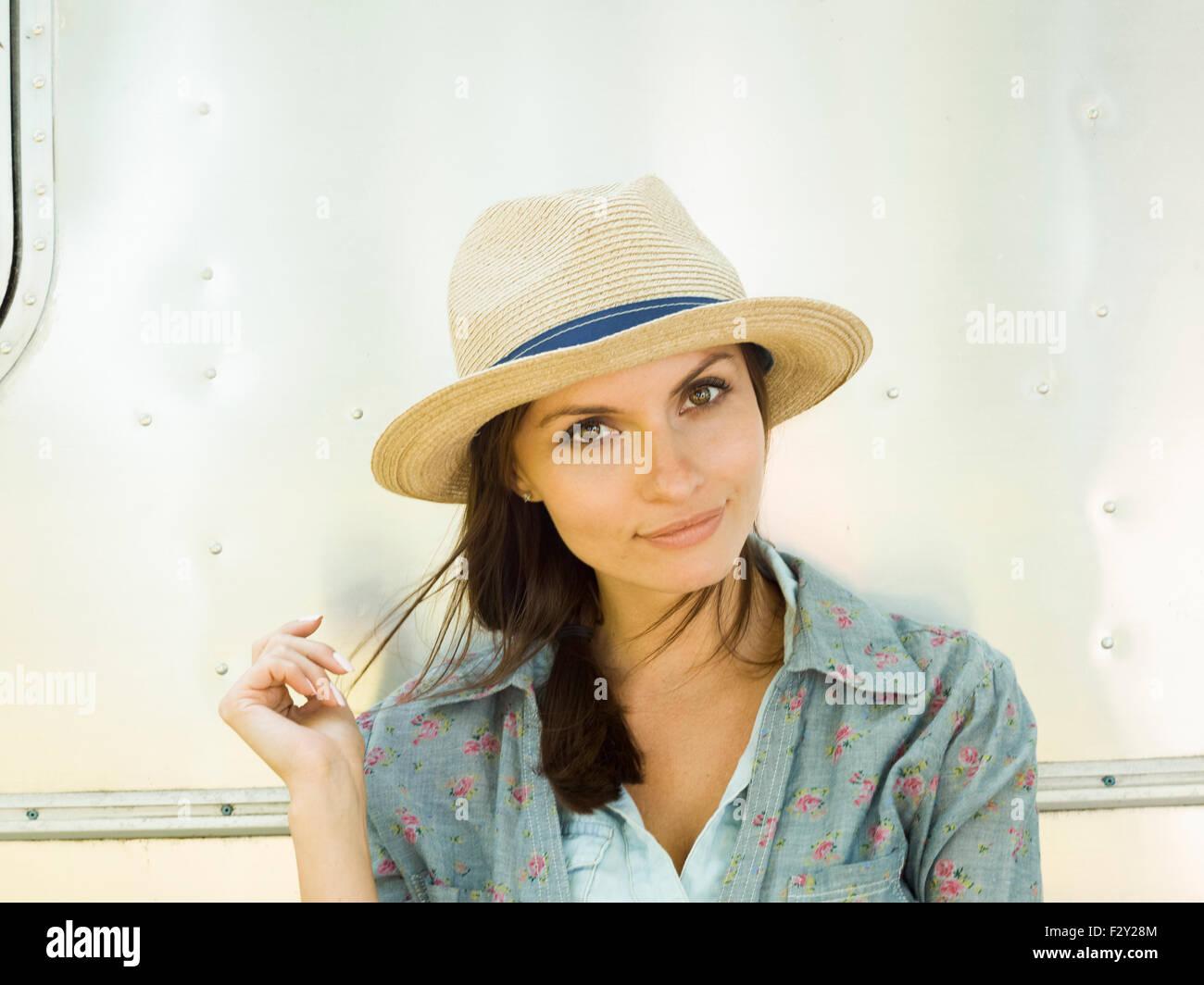 Una giovane donna in un cappello di paglia, la sua testa inclinata guardando curioso. Immagini Stock