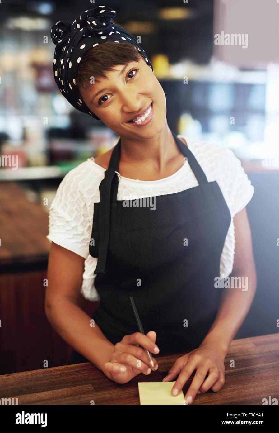 Sincera attraente giovane femmina African American coffee shop proprietario in piedi in un grembiule e bandana dietro Immagini Stock