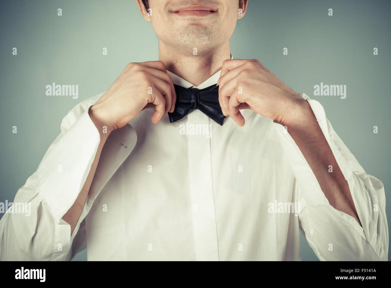 Primo piano su un felice giovane legatura di un filtro bow tie Immagini Stock