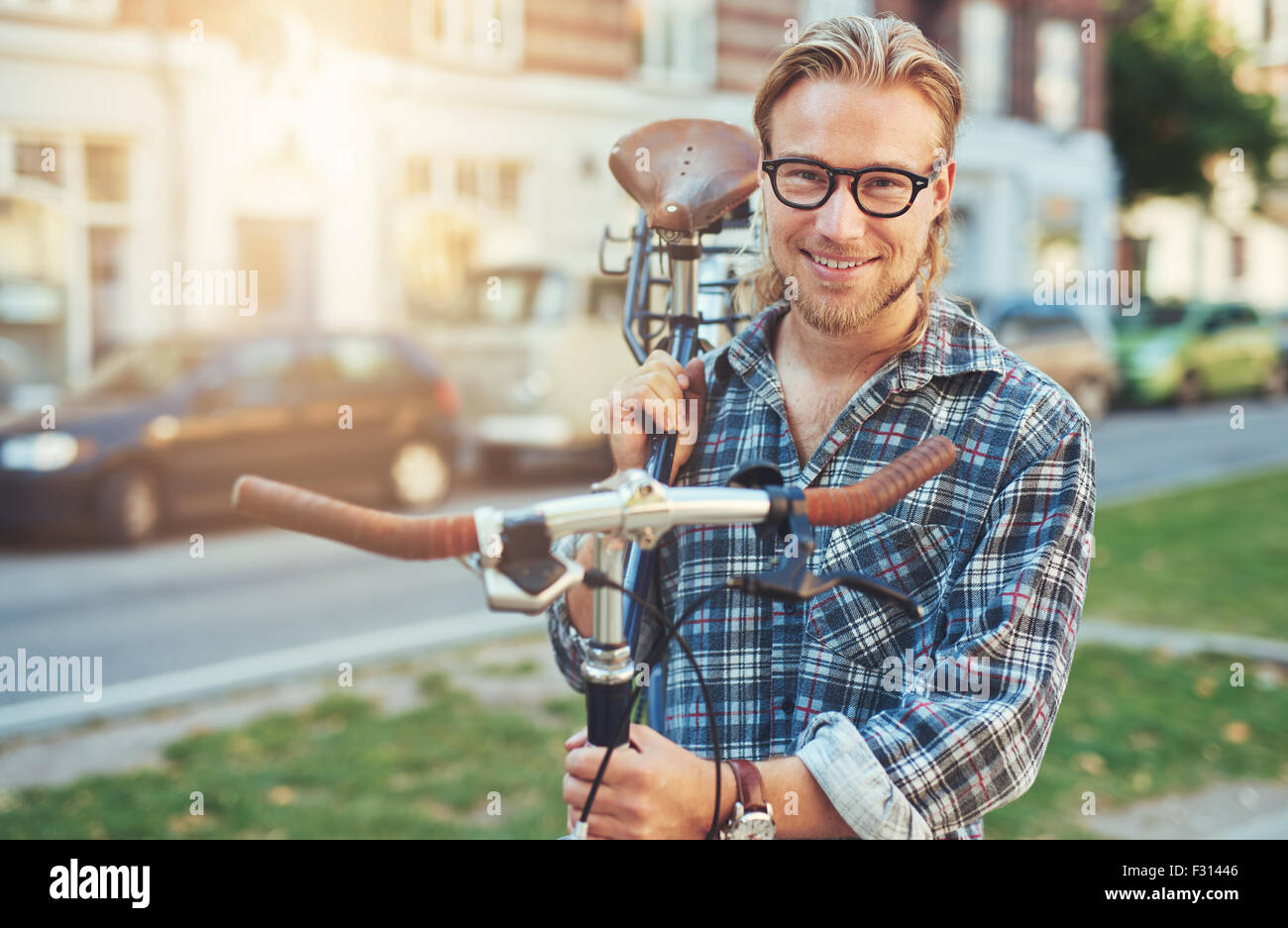 Giovane uomo lo stile di vita della città. Trasporto bici sulla sua spalla. Ritratto sorridente Immagini Stock
