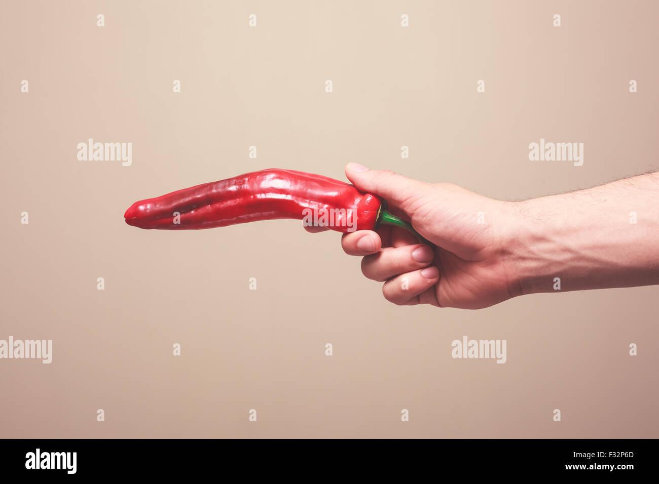 Una mano d'uomo è in possesso di un peperone rosso come una pistola Immagini Stock