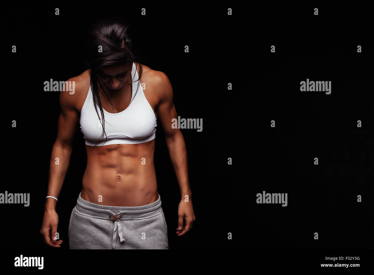 Immagine della donna fitness in abbigliamento sportivo guardando verso il basso. Giovane femmina modello con corpo Immagini Stock