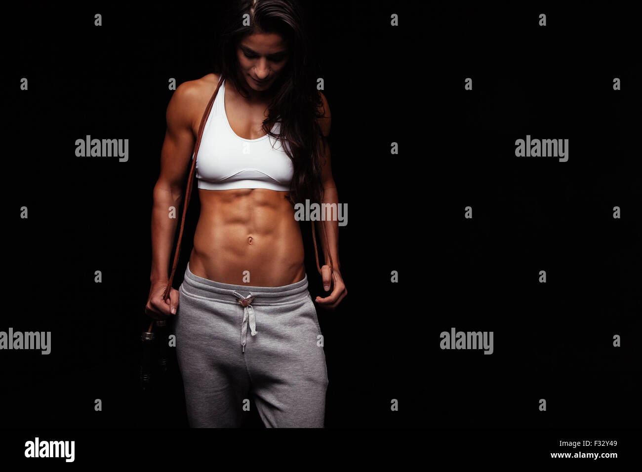 Ritratto di muscolare di giovane donna con un salto con la corda. Bodybuilder femminile con corda da salto guardando Immagini Stock