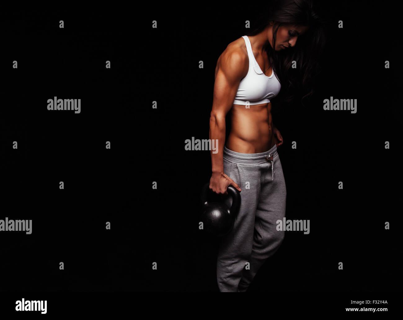 Donna muscolare facendo esercizio crossfit. Fitness resistente modello femminile con bollitore bell su sfondo nero. Immagini Stock