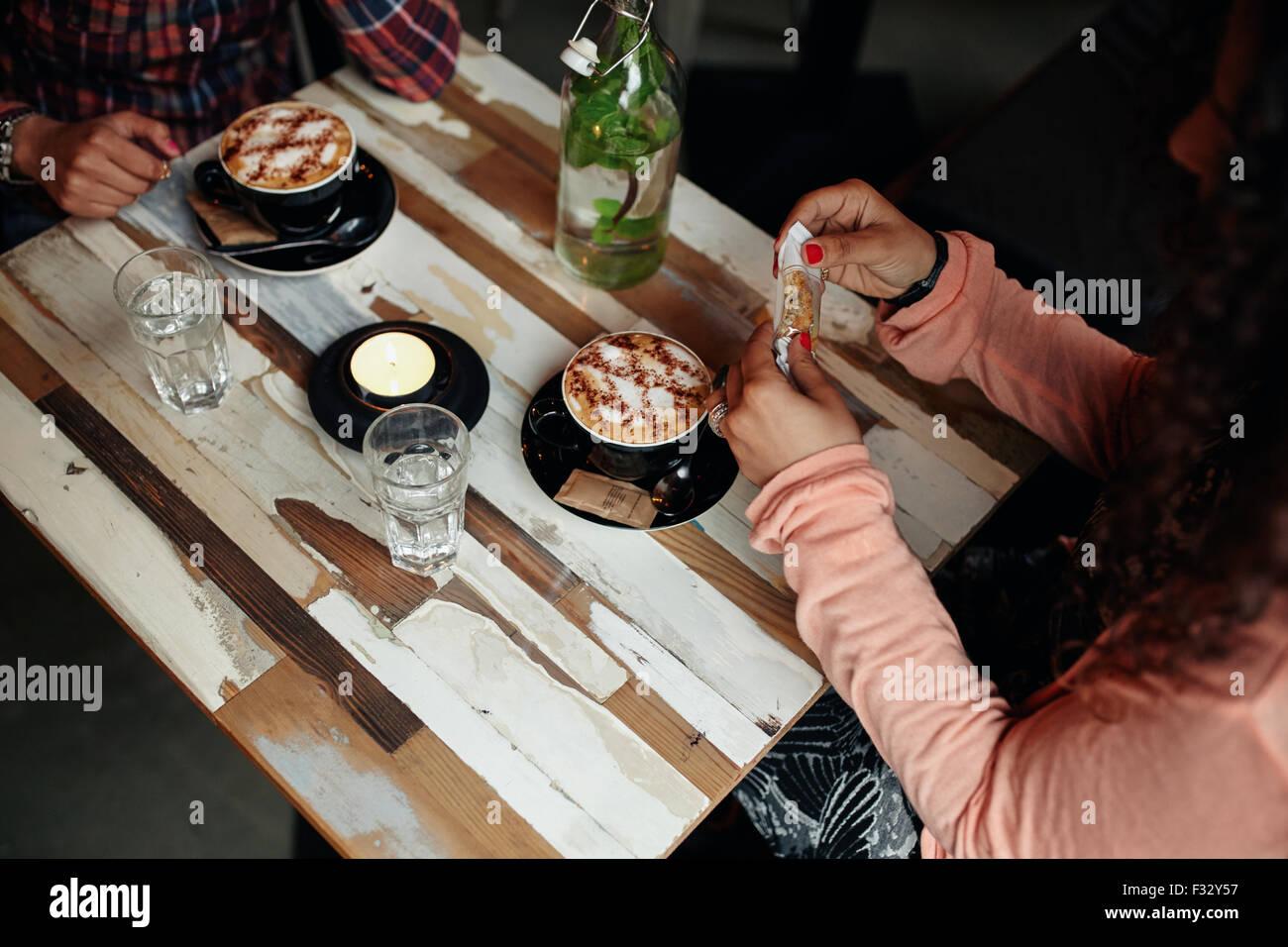 Direttamente sopra vista del caffè sul tavolo del bar. Due donne seduti al ristorante con tazza di caffè. Immagini Stock