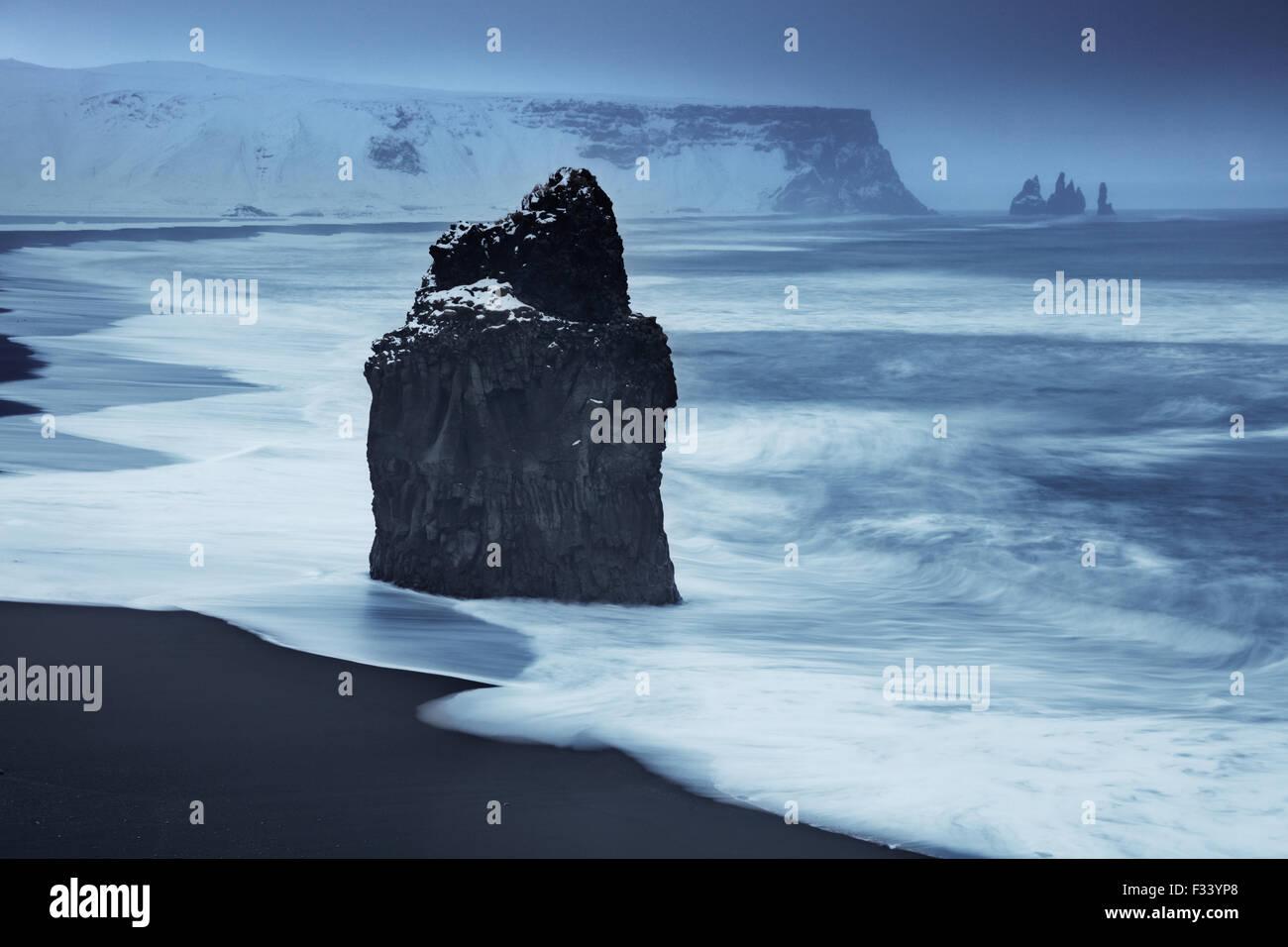 Onde che si infrangono sulla Reynisfjara con Reynisdranger oltre, Islanda Immagini Stock