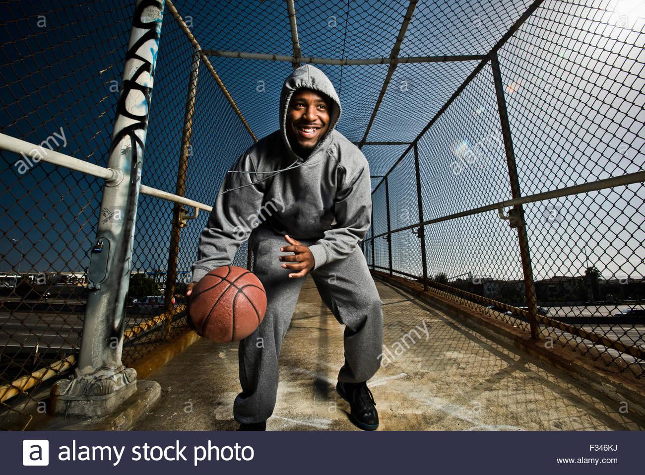 Un giovane uomo giocando con una palla da basket. Immagini Stock
