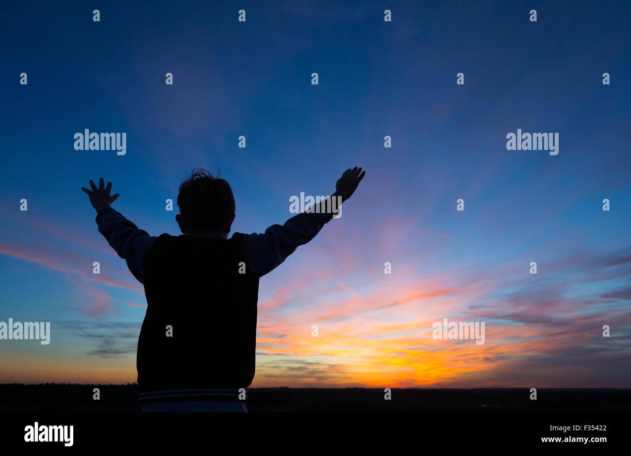 Silhouette di un ragazzo giocando fuori al tramonto Foto Stock