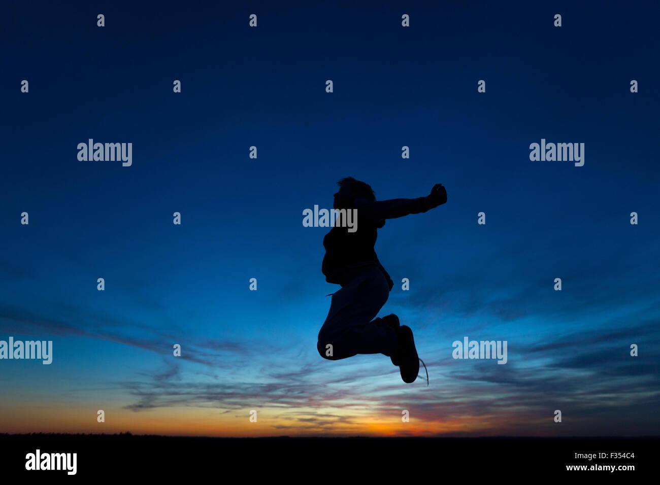Silhouette di un ragazzo giocando fuori al tramonto Immagini Stock