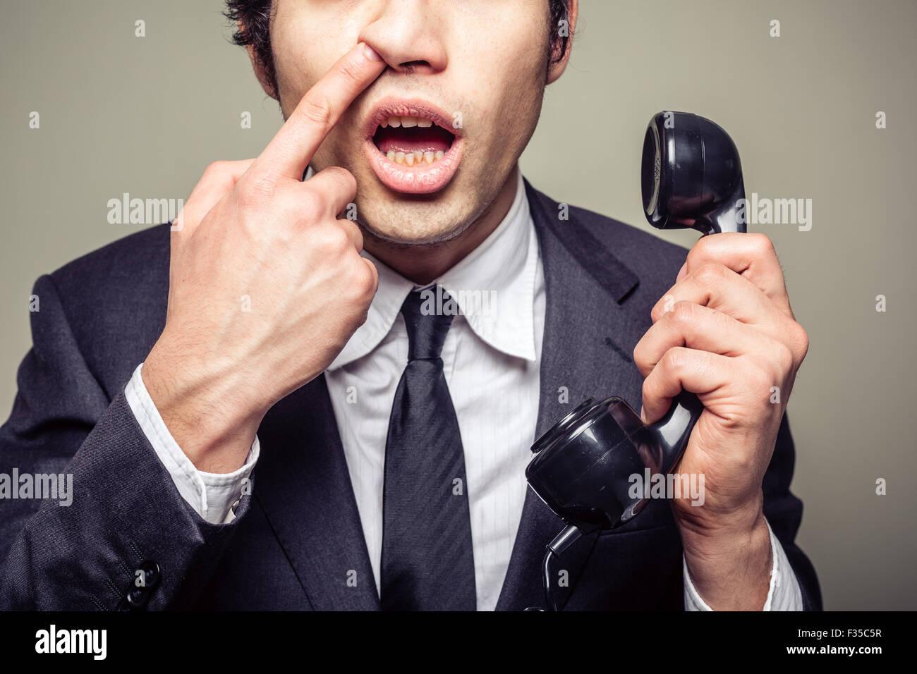 Giovane imprenditore incompetenti è sul telefono e il prelievo è il suo naso Immagini Stock