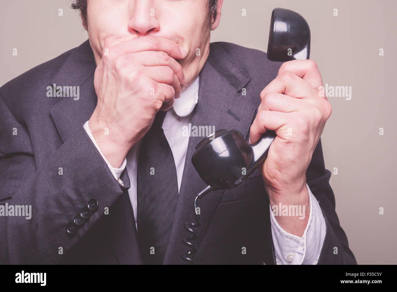 Un giovane imprenditore è al telefono e che copre la sua bocca in stato di  shock 5d3db1822066