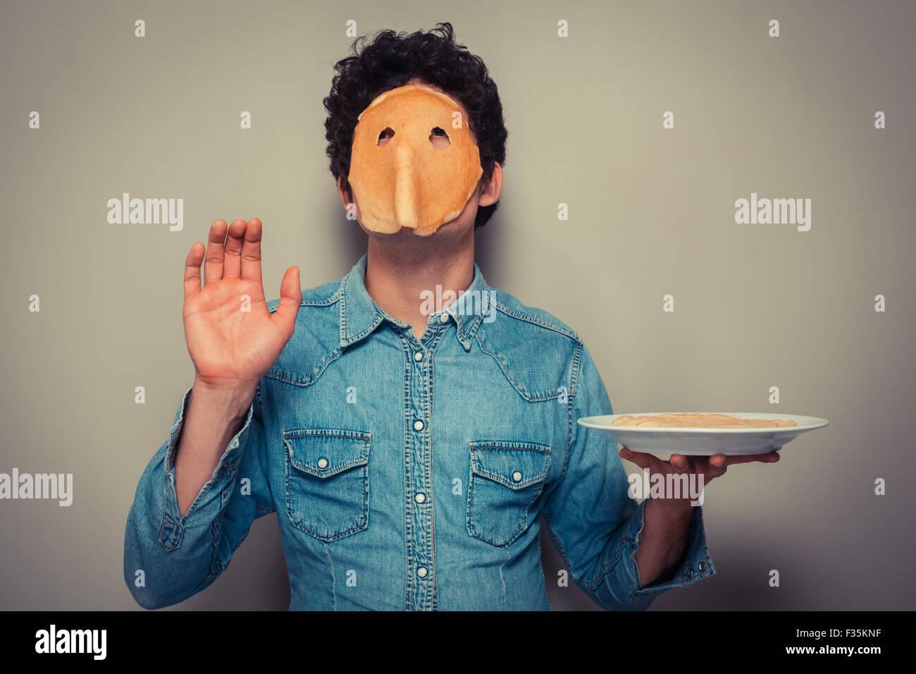 Giovane uomo ha tagliato eyeholes in un pancake e indossarlo sul suo volto Immagini Stock