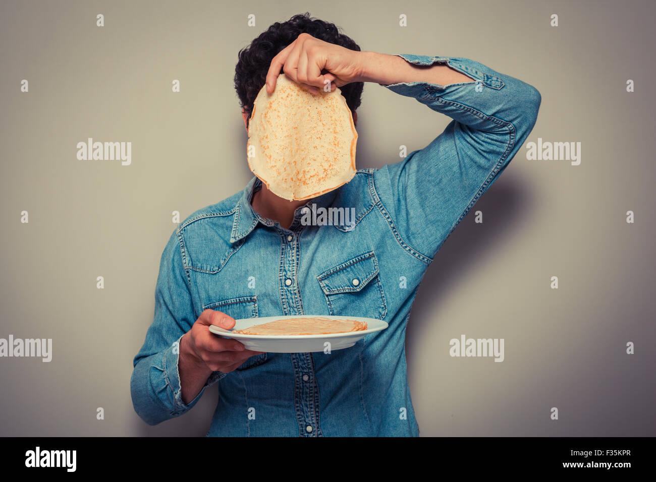 Giovane uomo si nasconde il suo volto dietro un pancake Immagini Stock