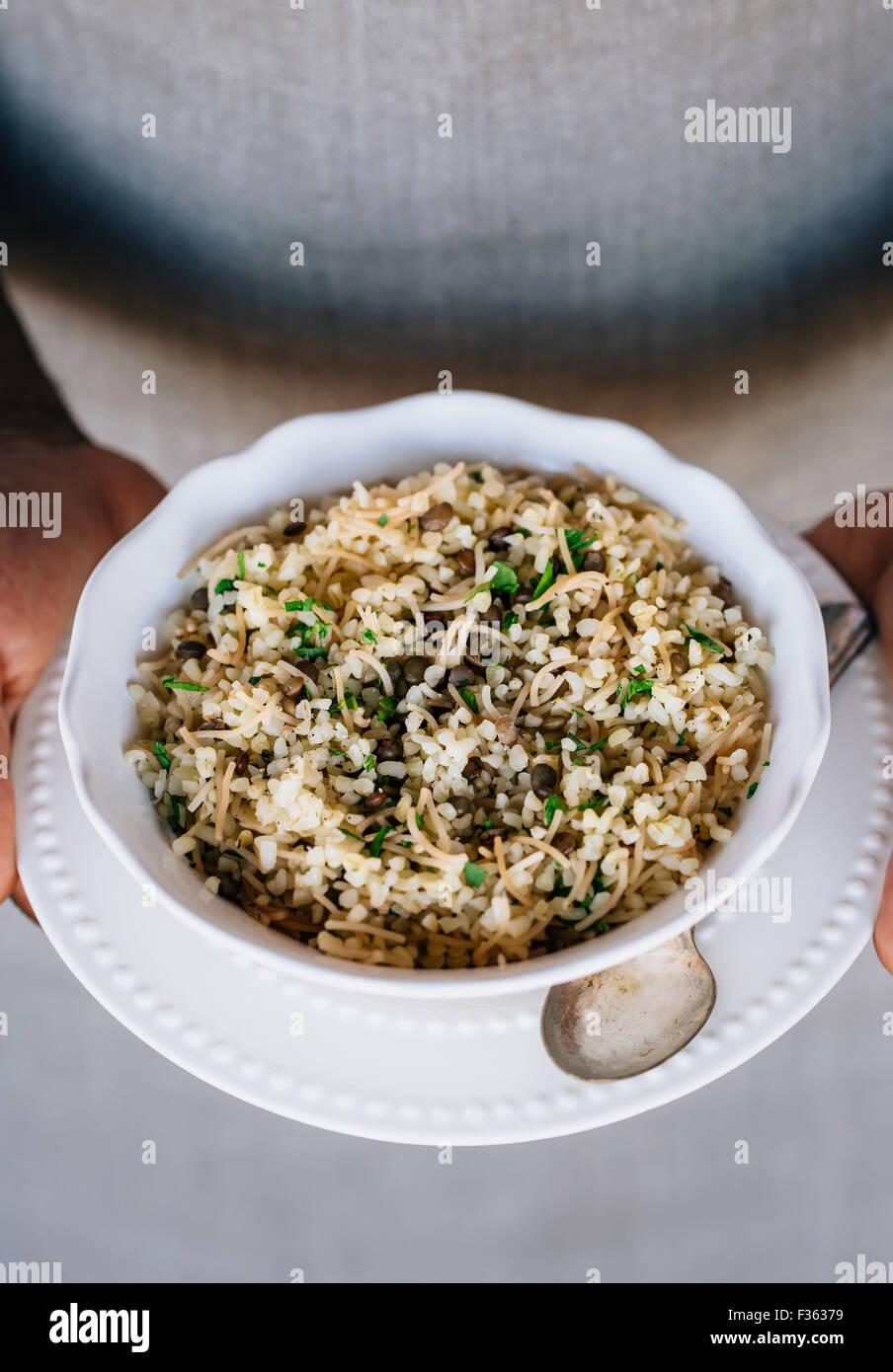 Una tazza di bulgur pilaf mescolato con le lenticchie e le erbe fresche sono nelle mani di un uomo che indossa un Immagini Stock