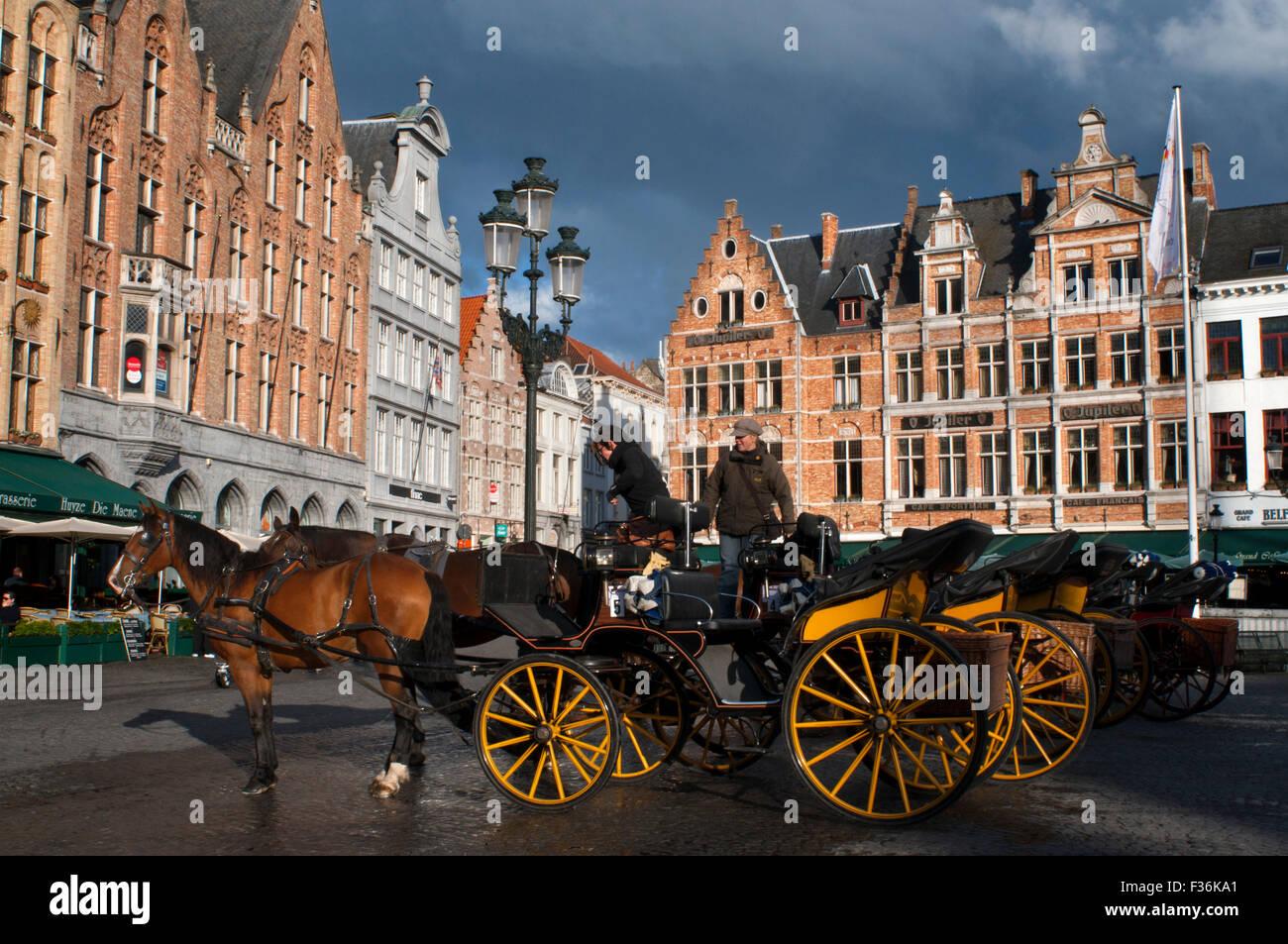 Bruges con carrozza a cavalli. La posizione centrale della piazza del mercato indica che questo è stato il Immagini Stock