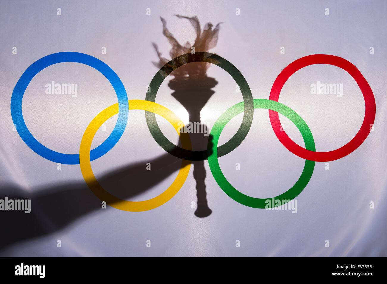 RIO DE JANEIRO, Brasile - 3 febbraio 2015: Silhouette della mano che tiene lo sport torcia dietro gli anelli di Immagini Stock