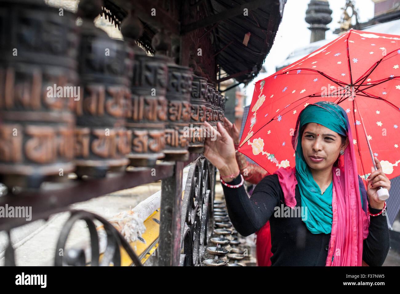 Una signora pregando con pregare wheles a Swayambhunath temple Kathmandu, Nepal Immagini Stock