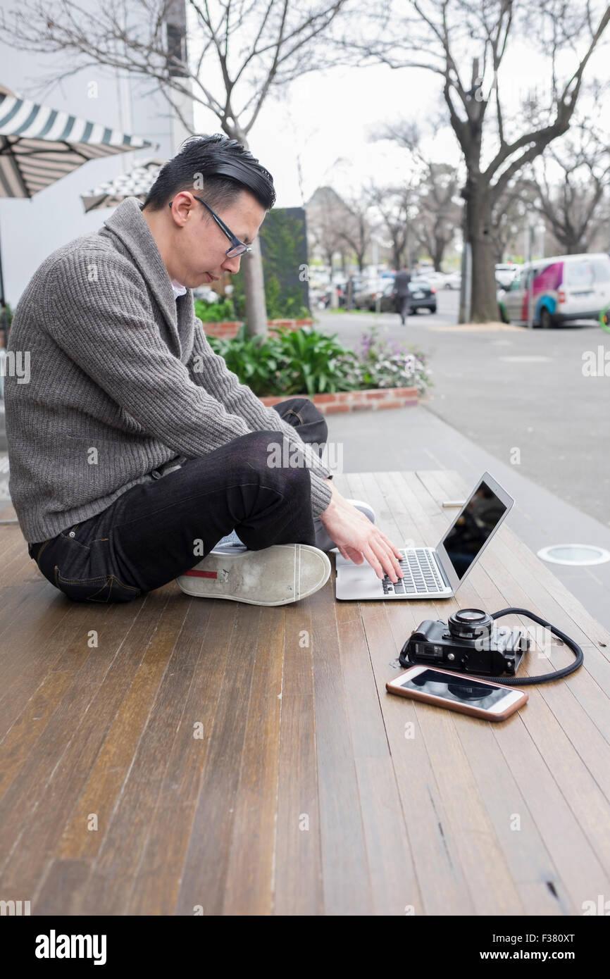 Uomo che utilizza un notebook per lavorare in esterno, con telecamera e telefono Immagini Stock