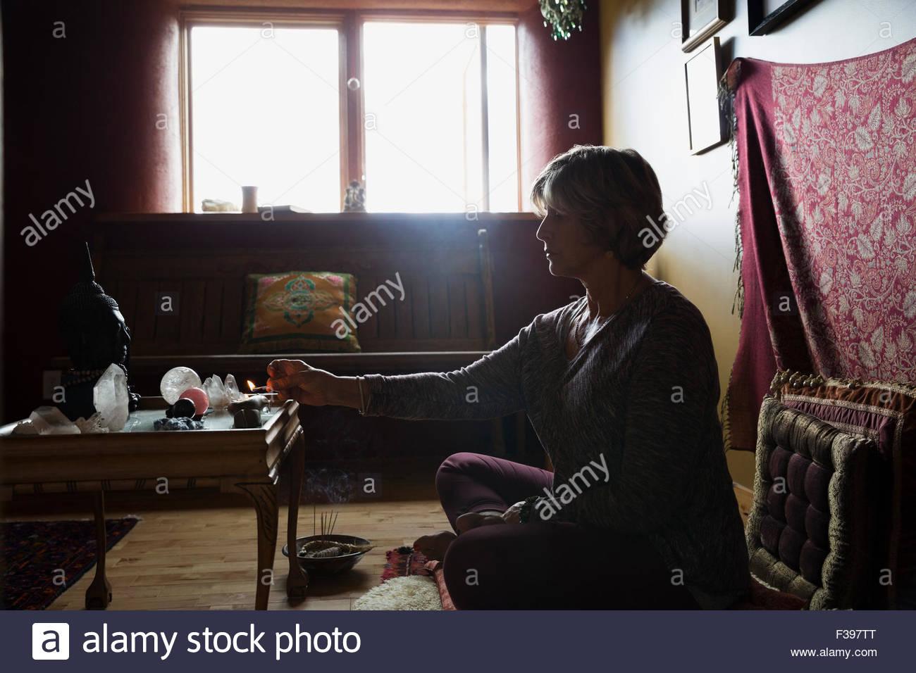 Senior donna incenso di illuminazione nella stanza di meditazione Foto Stock