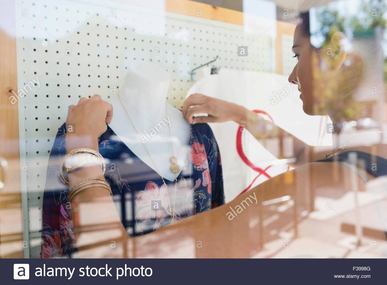 Lavoratore disponendo negozio di abbigliamento window display manichino Immagini Stock