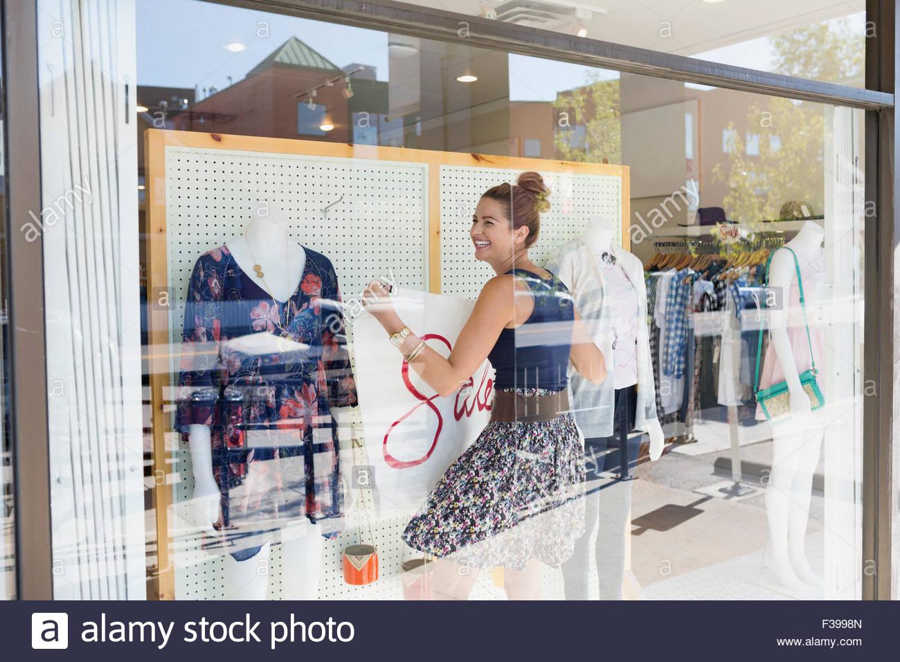 Lavoratore sorridente appendere vendita segno negozio di abbigliamento finestra Immagini Stock