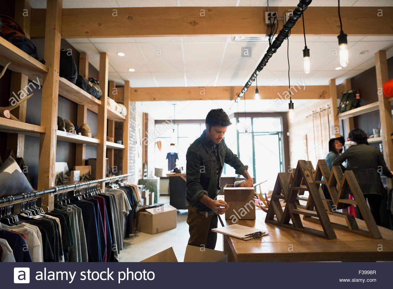 Lavoratore di disimballare il nuovo inventario nel negozio di abbigliamento Immagini Stock