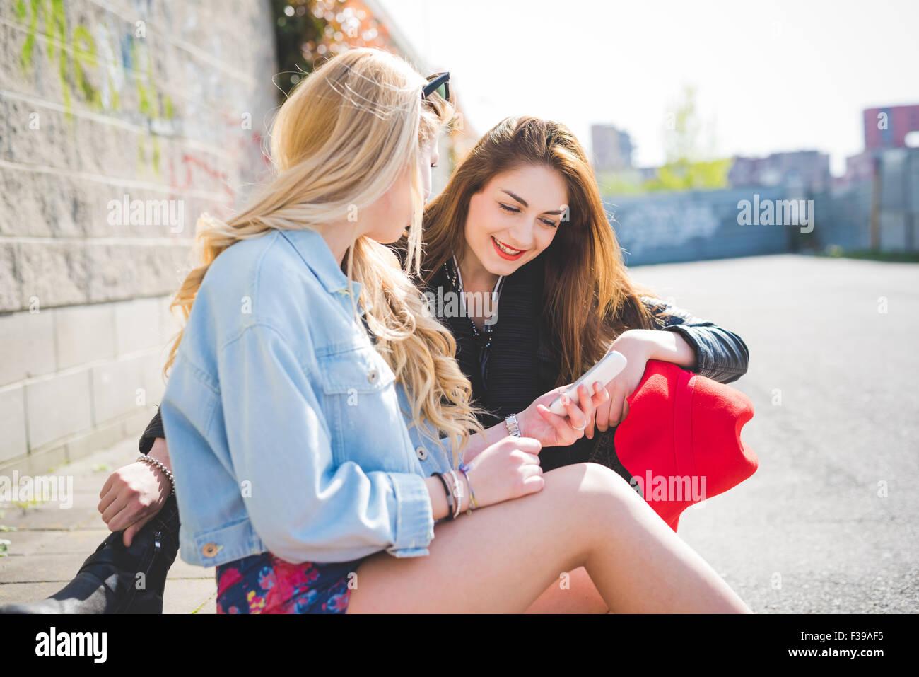 Due giovani bionda e bruna ragazze seduta sul pavimento in chat e utilizza  lo smartphone 32931efeb0d6