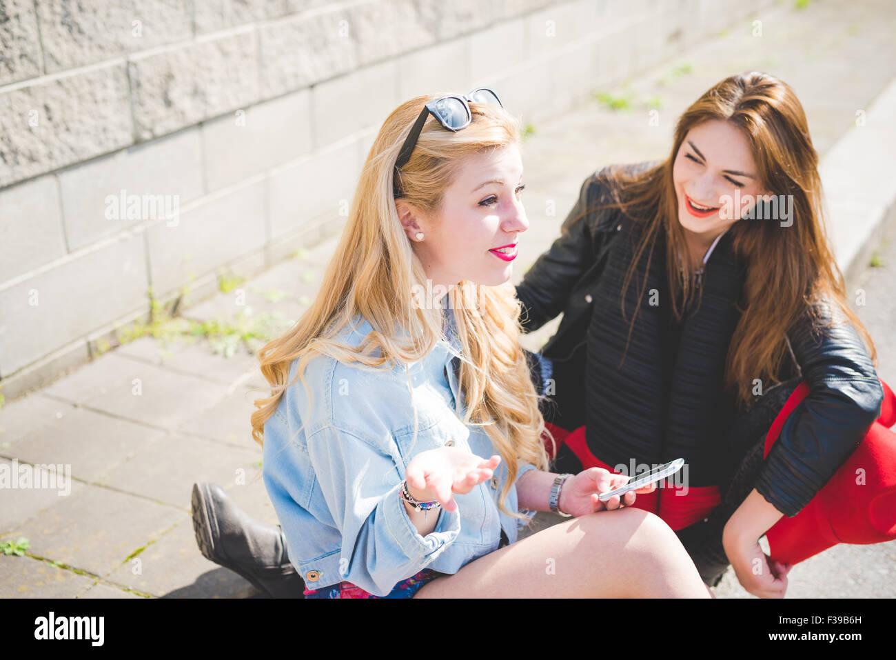Due bellissime bionde e bruna amici seduti sul pavimento a chattare e  divertirsi utilizzando uno smartphone 01fcc89dbaf8