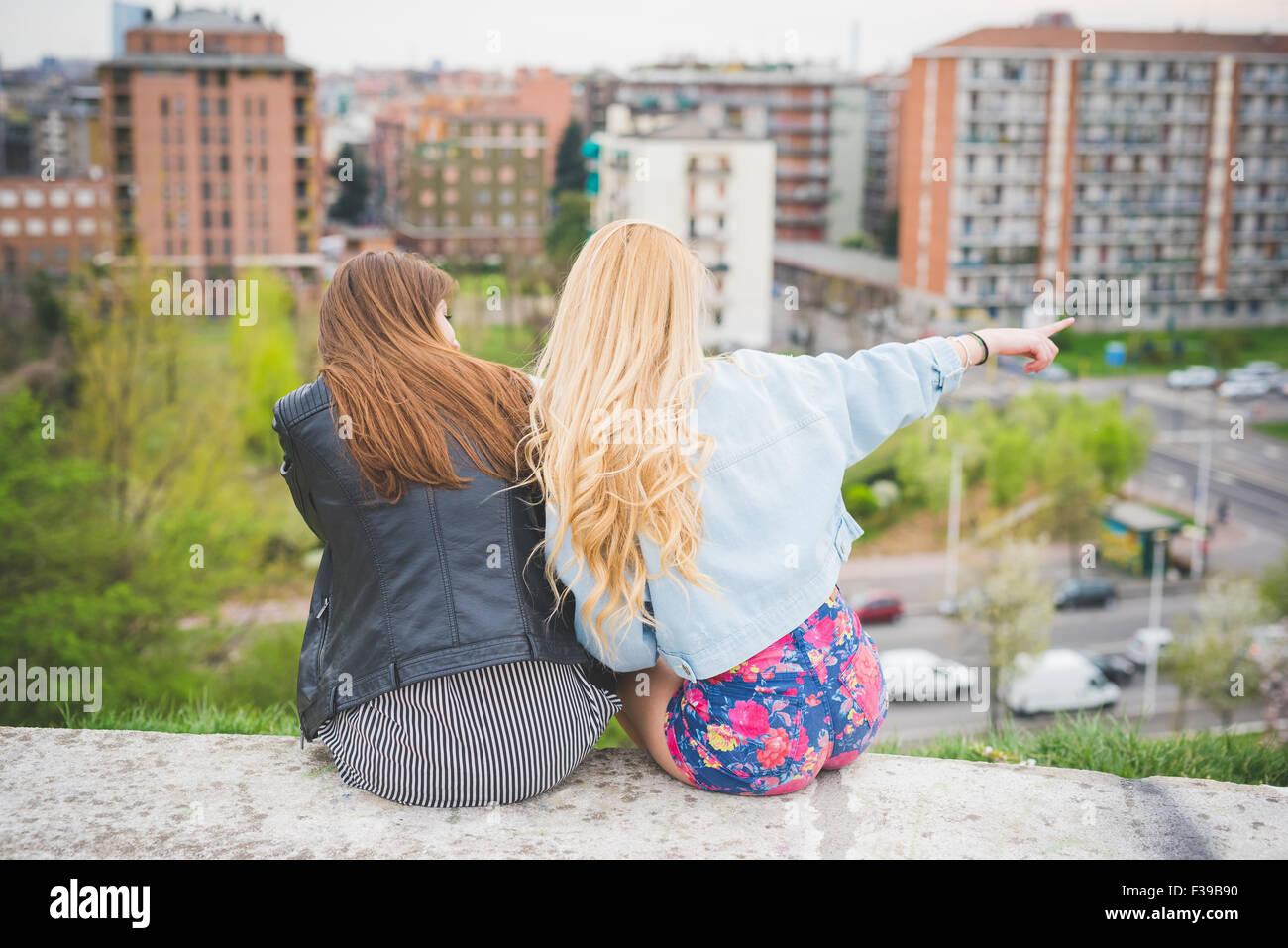 Due giovani bionda e bruna Ragazze in Chat seduto su di una piccola parete  con la città sullo sfondo 6d7055b3d2ac