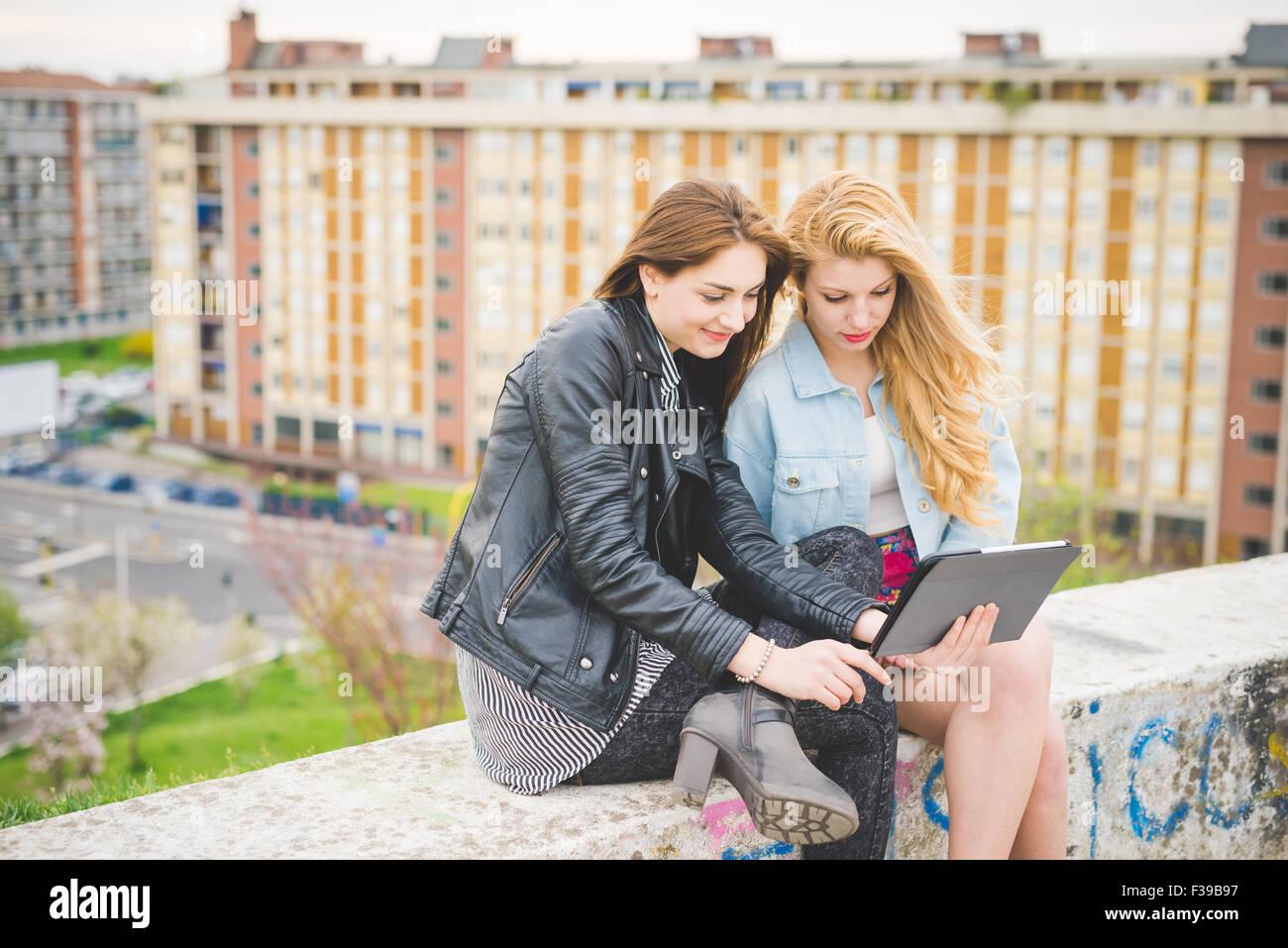 Due giovani bionda e bruna ragazze utilizzando tablet seduti su un muretto 6ea28d4ee667