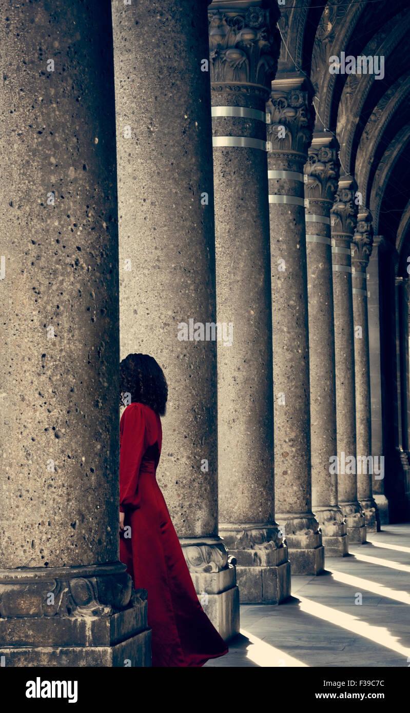 Misteriosa donna in abito rosso dietro la colonna Immagini Stock