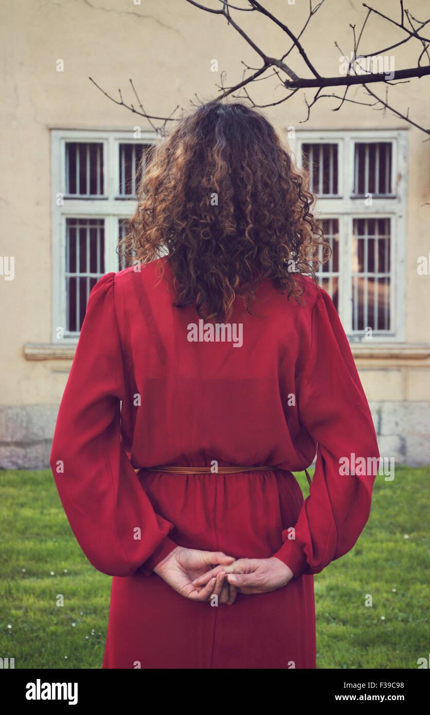 Donna in abito rosso in piedi all'aperto, vista posteriore Immagini Stock