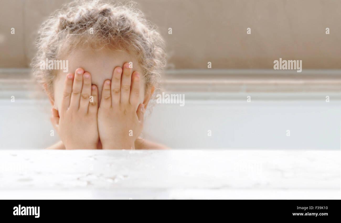 Ritratto di una ragazza seduta in una vasca da bagno che ricopre la faccia con le mani Immagini Stock