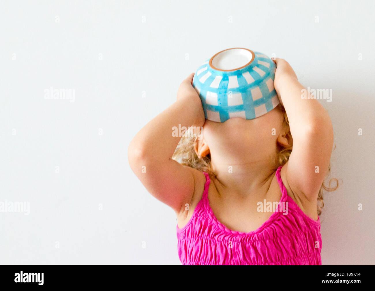 Ragazza con testa indietro azienda ciotola di cereali per la sua bocca Immagini Stock