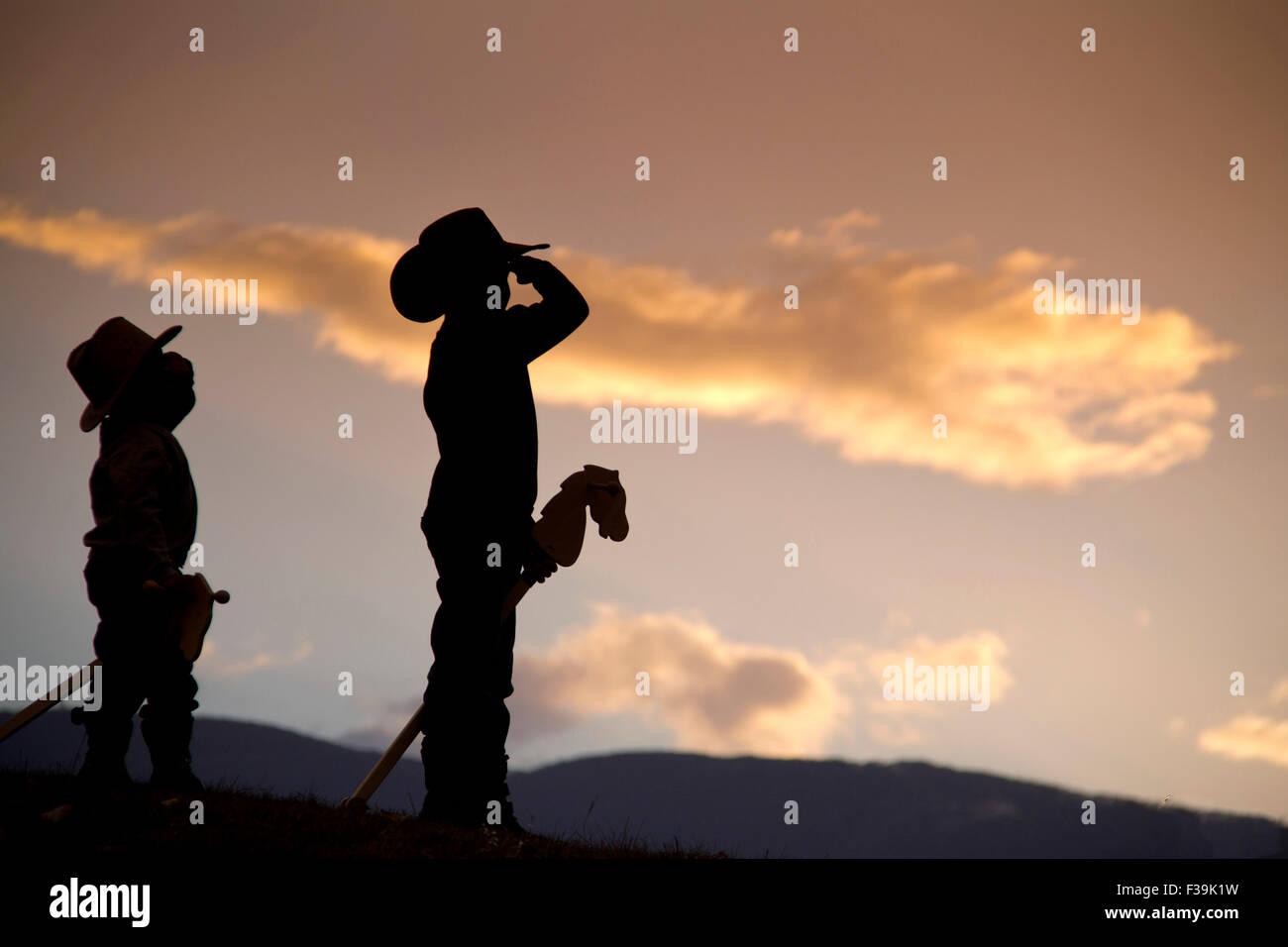 Silhouette di due ragazzi con i cavalli hobby fingendo di essere cowboy salutando con orgoglio Immagini Stock