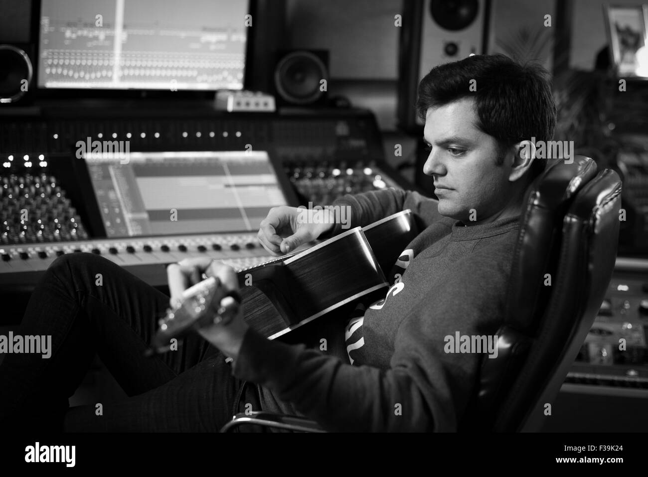 Uomo a suonare la chitarra in studio di registrazione Immagini Stock