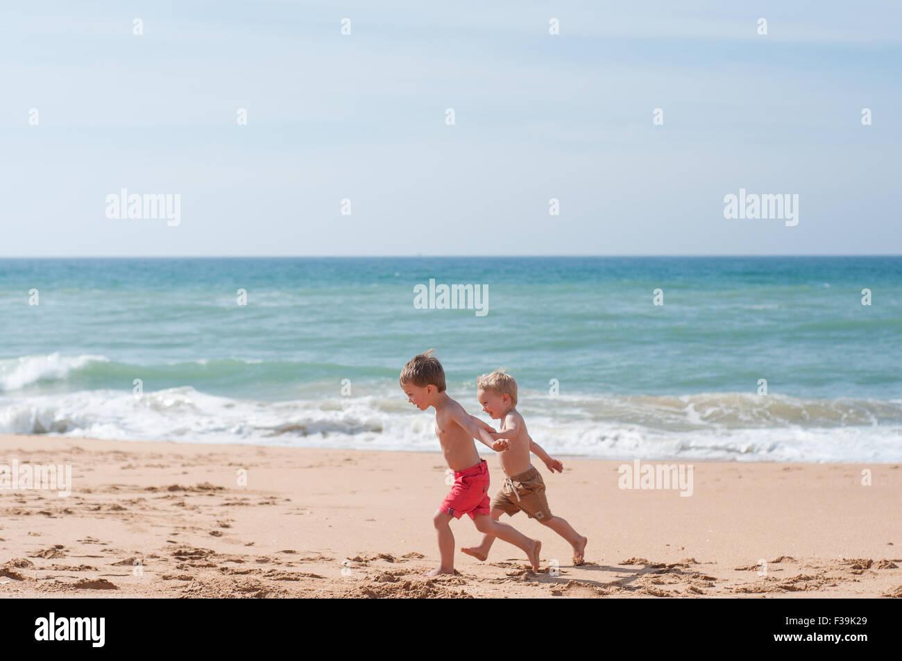 Due ragazzi che corre lungo la spiaggia Immagini Stock