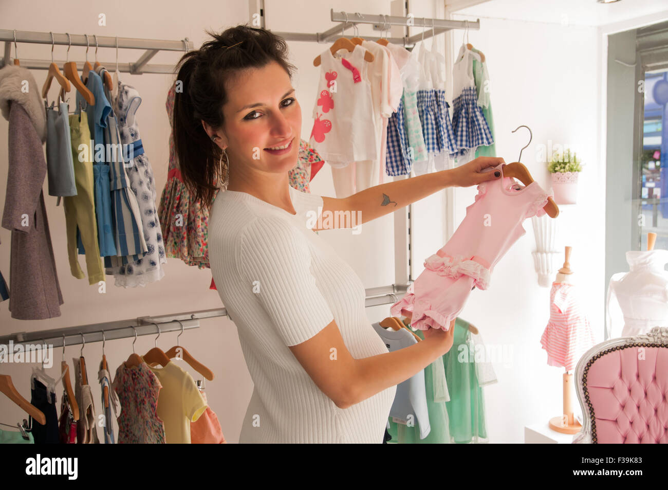 Ritratto di un sorridente donna incinta in un negozio guardando i vestiti  del bambino Immagini Stock 838dc4df461